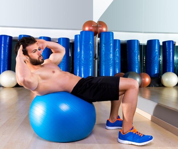 Fitball abdominal crunch homem bola suíça no ginásio Foto Premium
