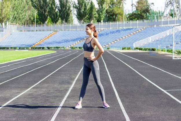 Fitness atraente mulher warm-up antes de executar na pista do estádio no dia ensolarado de verão Foto Premium