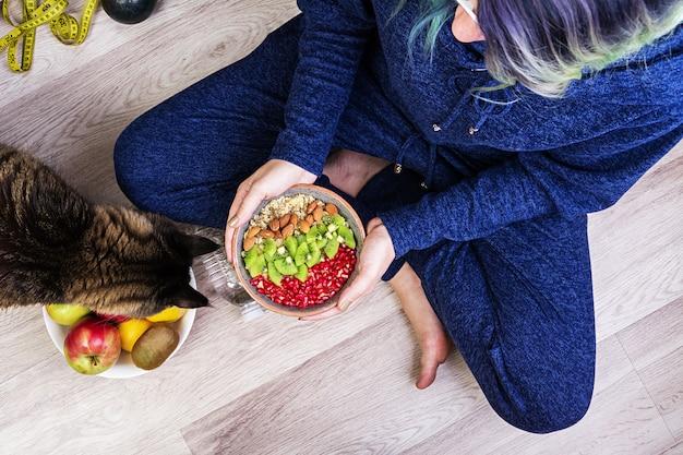 Fitness e conceito de estilo de vida saudável. fêmea está descansando e comendo uma aveia saudável depois de um treino. vista do topo. Foto gratuita