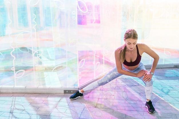 Fitness jovem fazendo exercícios de alongamento na sala Foto gratuita