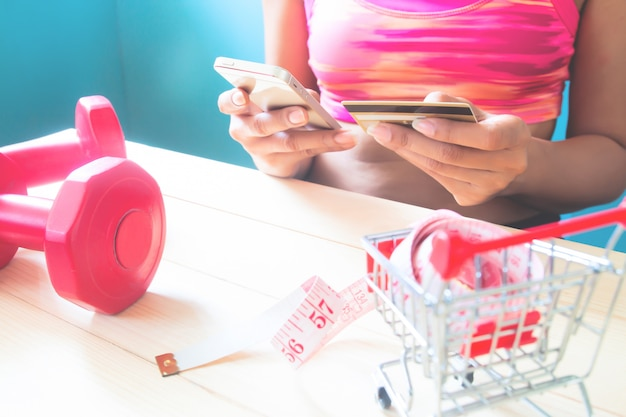 Fitness jovem saudável usando telefone celular e segurando o cartão de crédito, compras on-line Foto Premium