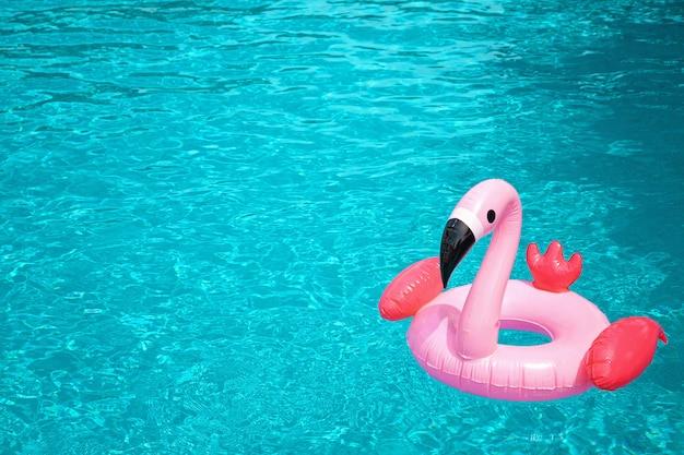 Flamingo rosa inflável na água azul da piscina Foto Premium