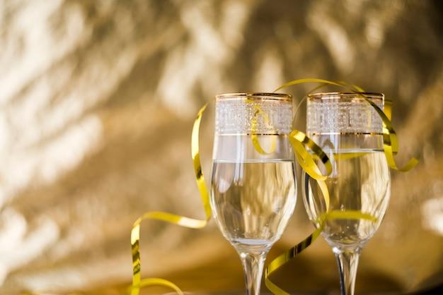 Flâmulas douradas em taças de champanhe transparentes contra fundo desfocado Foto gratuita