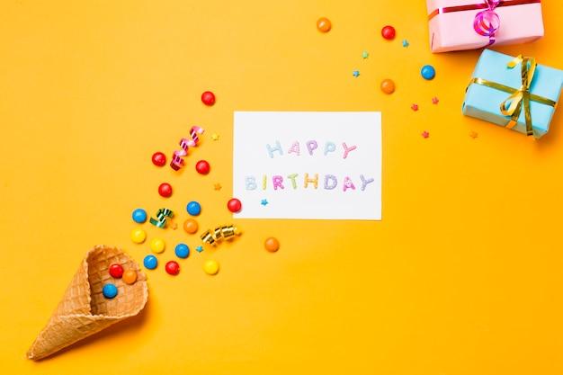 Flâmulas e pedras preciosas no waffle com feliz aniversário em papel contra o fundo amarelo Foto gratuita