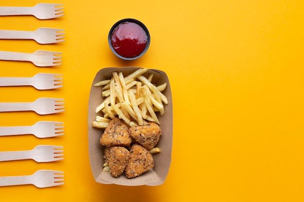 Flat lay arranjo com alimentos e garfos insalubres Foto gratuita