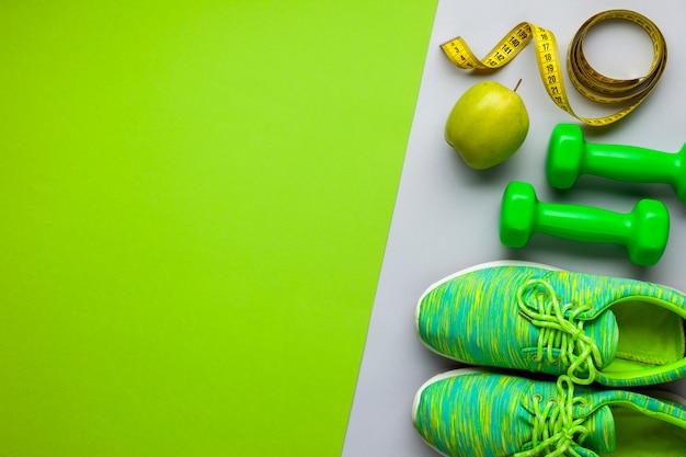 Flat lay arranjo com tênis e halteres Foto gratuita