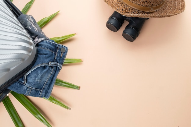 Flat lay cinza mala com jeans, binóculos, chapéu Foto Premium