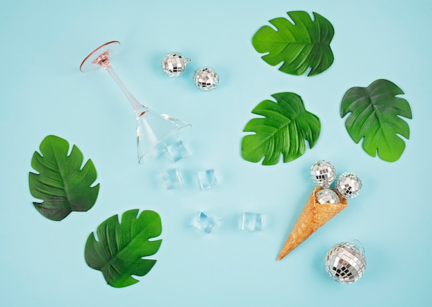 Flat lay com bolas de discoteca no cone, cubos de gelo, copo de coquetel Foto Premium