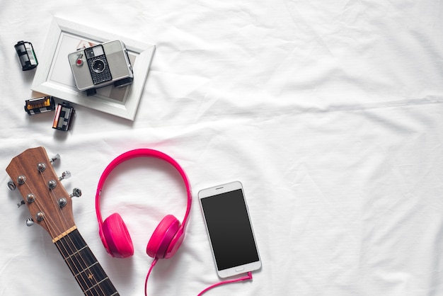 Flat lay conceito de estilo de vida com smartphone, fone de ouvido, câmera no fundo branco da tela Foto Premium