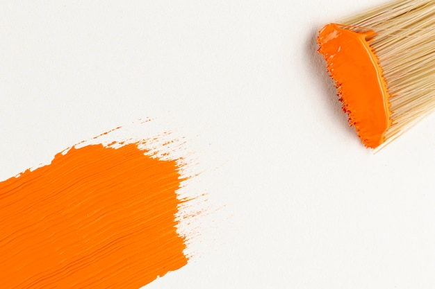 Flat lay de pincelada e pinceladas de tinta laranja Foto gratuita