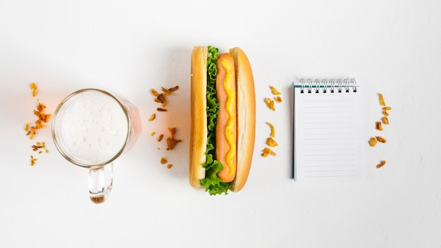 Flat lay hotdog com mock-up do bloco de notas Foto gratuita
