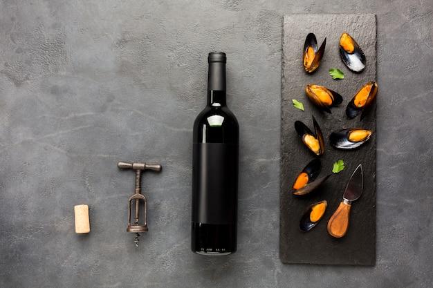Flat-lay mexilhões cozidos em ardósia com garrafa de vinho Foto gratuita