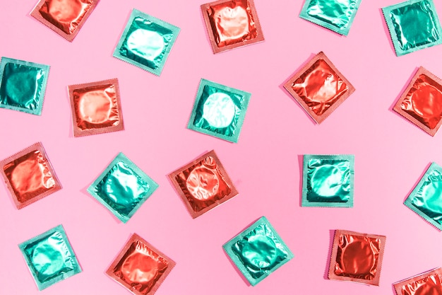 Flat lay preservativos em invólucros vermelhos e verdes Foto gratuita