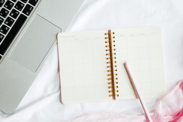 Flat leiga cama espaço de trabalho com laptop, caderno, caneta Foto Premium