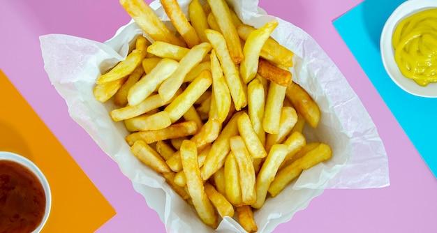 Flat leigos de batata frita com mostarda e ketchup Foto gratuita