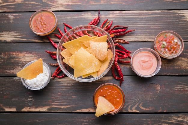 Flat leigos de nachos com pimenta e molhos Foto gratuita
