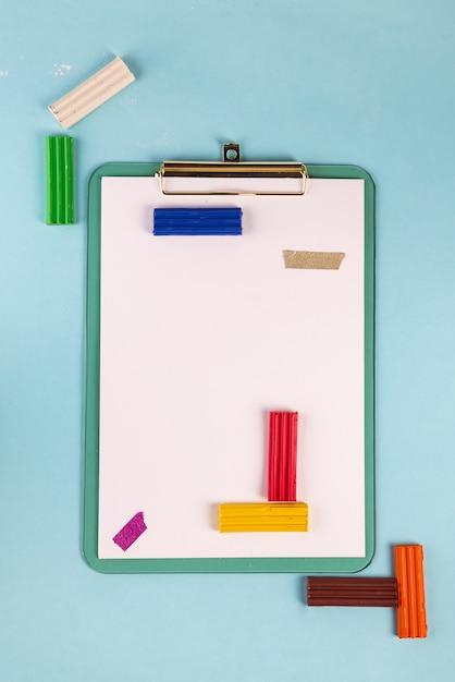 Flat leigos prancheta azul com plasticina em um jogo azul e tetris Foto Premium