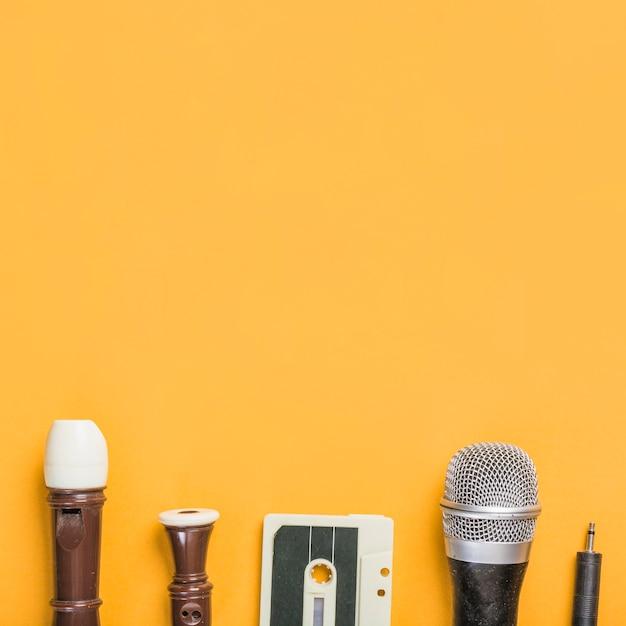 Flauta de bloco; fita cassete; microfone em fundo amarelo Foto gratuita