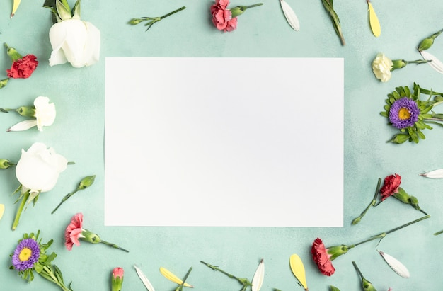 Flay lay quadro de flores de cravo com cartão branco Foto gratuita