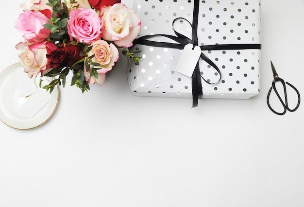 Flay leigos. as rosas brancas do ramalhete da tabela scissors o feriado festivo e branco dos bonsais da etiqueta. Foto Premium