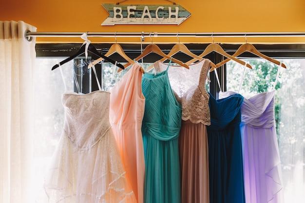 Flecha com letras 'praia' pendura sobre os vestidos pastel Foto gratuita