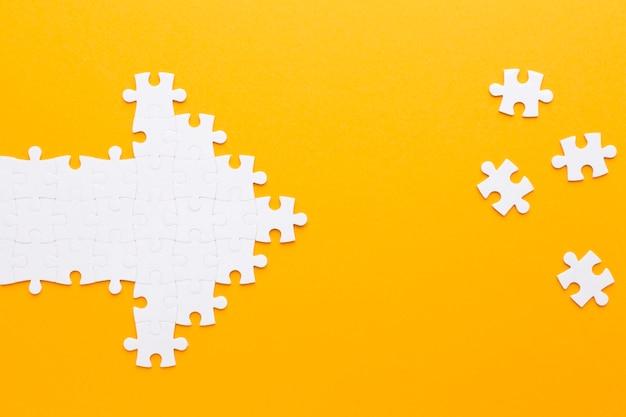 Flecha feita de peças de quebra-cabeça, apontando para outras peças Foto gratuita