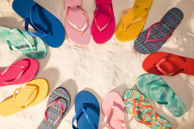 Flip-flops coloridos na areia Foto gratuita
