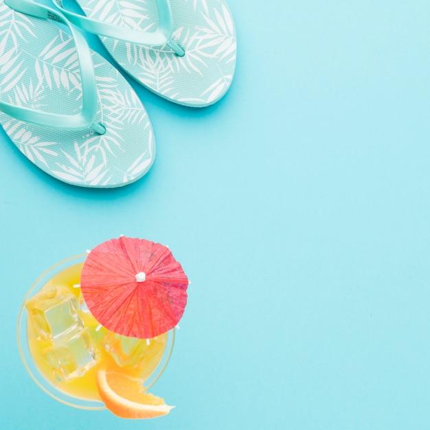 Flip-flops e coquetel refrescante em fundo colorido Foto gratuita