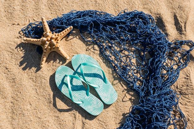 Flip flops e estrelas do mar com malha na areia Foto gratuita