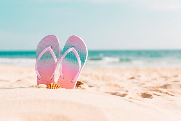 Flip flops na praia Foto gratuita
