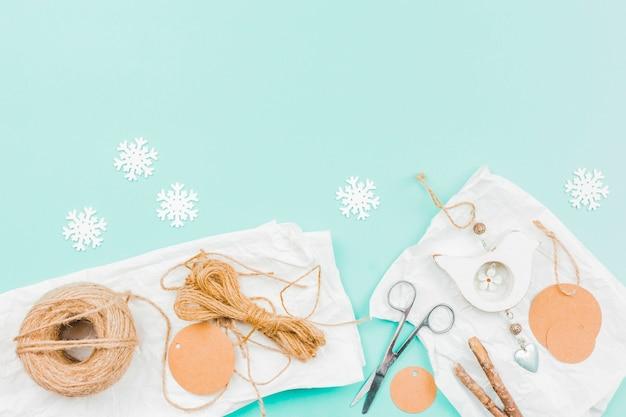 Floco de neve de papel branco; fio de juta; papel; tesoura e vara para fazer parede pendurado mostrar peça no pano de fundo turquesa Foto gratuita