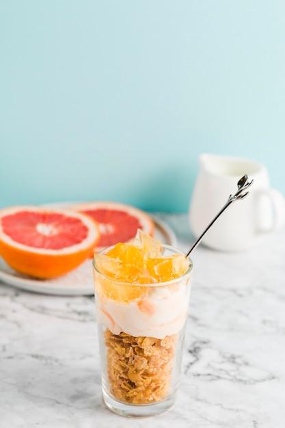 Flocos de milho de alto ângulo com iogurte e frutas em vidro Foto gratuita