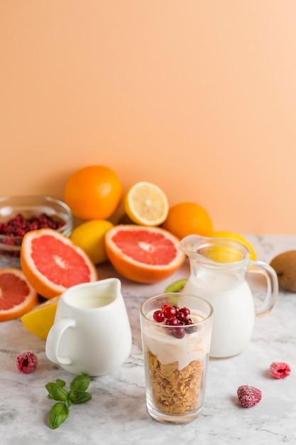 Flocos de milho e iogurte de alto ângulo em vidro com mik de frutas Foto gratuita