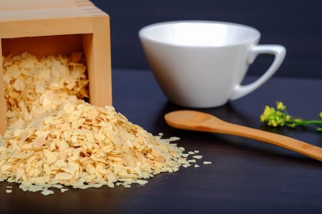 Flocos de milho em caixa de madeira sobre um fundo escuro de madeira e cópia Foto Premium