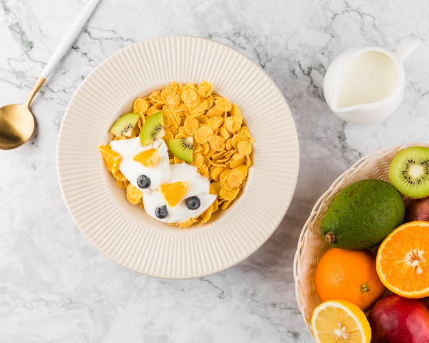 Flocos de milho plana leigos com iogurte e frutas Foto gratuita