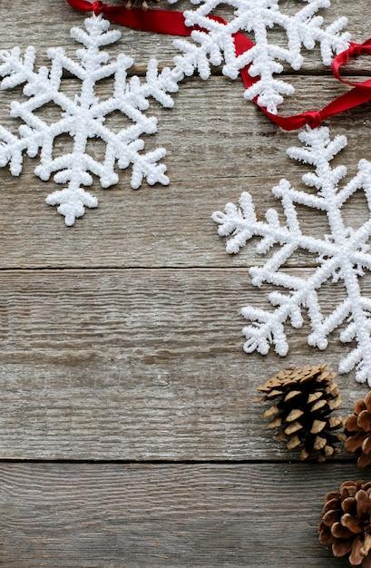 Flocos de neve, pinhas e fita vermelha Foto gratuita