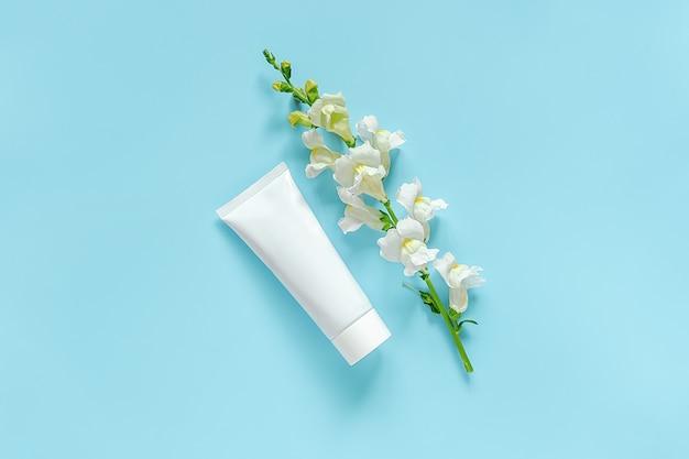 Flor branca e cosmético, tubo branco médico para creme, pomada, creme dental. cosméticos orgânicos naturais Foto Premium
