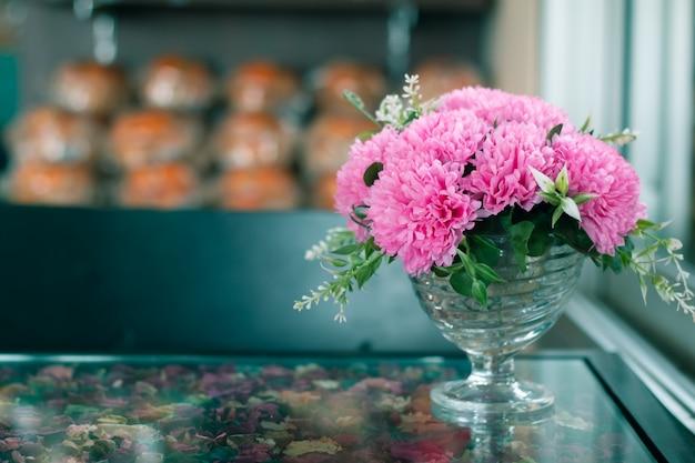Flor cor-de-rosa artificial na tabela de vidro com espaço da cópia para o fundo do amor Foto Premium