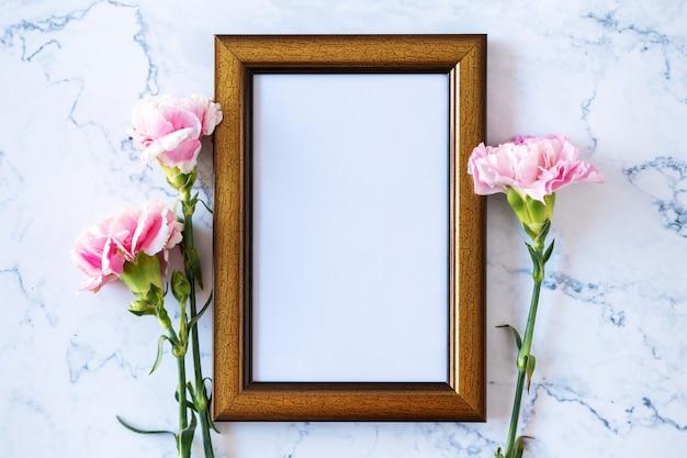 Flor cravo na moldura em branco sobre fundo de mármore, dia dos namorados, dia das mães ou aniversário Foto Premium
