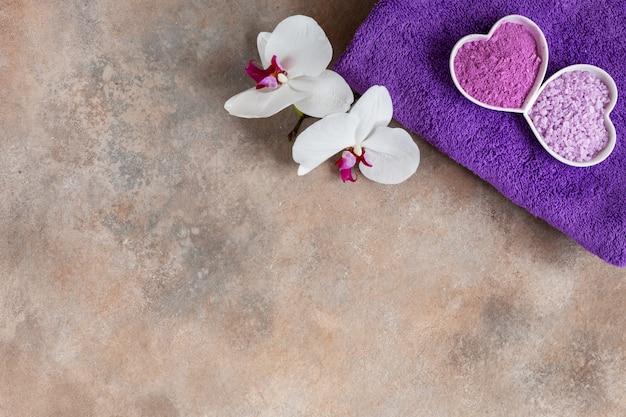 Flor da orquídea, sal do mar do aroma, argila cosmética natural, e toalha. Foto Premium