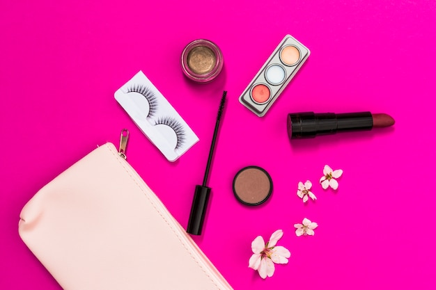 Flor de primavera; cílios; sombra; batom; escova de rímel e flor com bolsa de maquiagem rosa em fundo rosa Foto gratuita