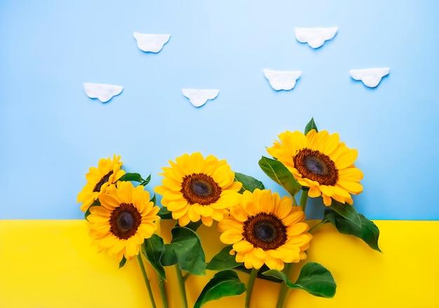 Flor de sun isolada sobre uma bandeira ucraniana. girassóis pequenos brilhantes no fundo amarelo e azul. mock-se modelo. copie o espaço para texto Foto Premium