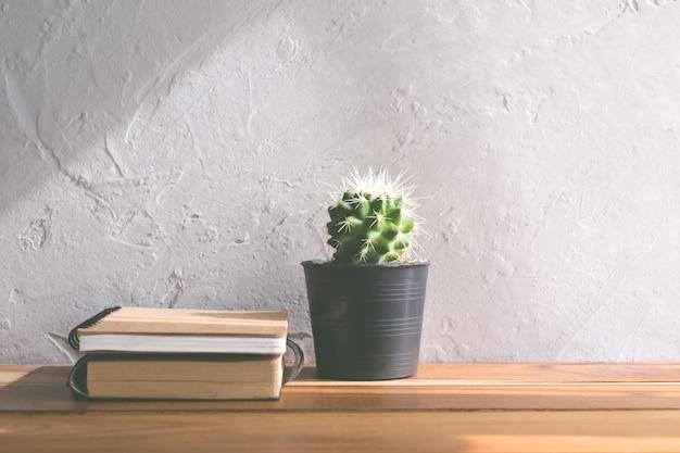 Flor do cacto com o caderno no conceito interior moderno do fundo da tabela de madeira. Foto Premium