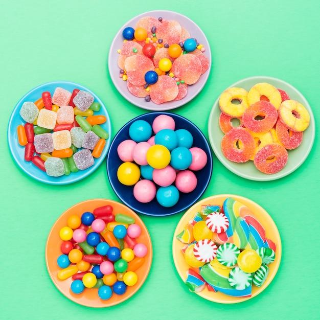 Flor feita de taças com doces na mesa Foto gratuita