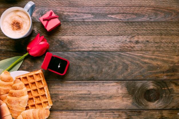 Flor fresca, padaria, anel na caixa de presente e copo de bebida Foto gratuita