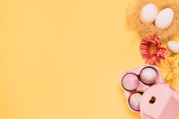 Flor gerbera e ovos de páscoa coloridos com espaço da cópia para escrever o texto no fundo amarelo Foto gratuita
