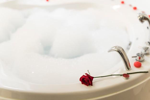 Flor na banheira de hidromassagem com água e espuma Foto gratuita