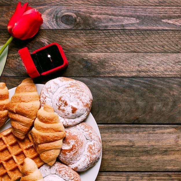 Flor, padaria no prato e anel na caixa de presente Foto gratuita