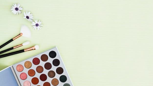 Flor; pincéis de maquiagem e paleta da sombra no pano de fundo texturizado hortelã Foto gratuita