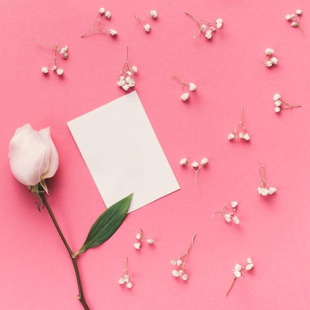 Flor rosa com papel pequeno na mesa Foto gratuita